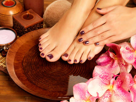 Closeup photo of a female feet at spa salon on pedicure procedure. Female legs in water decoration  the flowers. photo