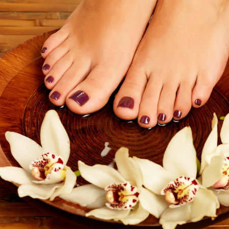 Closeup photo of a female feet at spa salon on pedicure procedure. Legs care concept