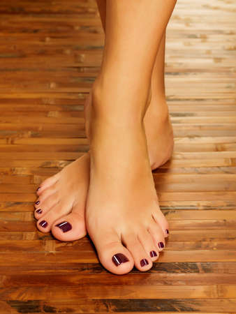Closeup photo of a female feet at spa salon on pedicure procedure - Soft focus image photo