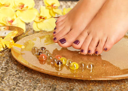 Closeup photo of a female feet at spa salon on pedicure procedure. Legs care concept. photo