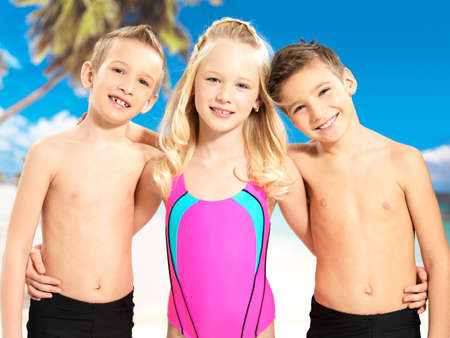 Portrait of the happy children enjoying at beach.  Schoolchild kids standing together in bright color swimwear. photo