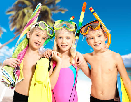 flippers: Portrait of the happy children enjoying at beach.  Schoolchild kids standing together in bright color swimwear with swimming mask on head .
