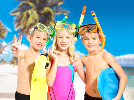 child swimsuit: Portrait of the happy children enjoying at beach.  Schoolchild kids standing together in bright color swimwear with swimming mask on head .