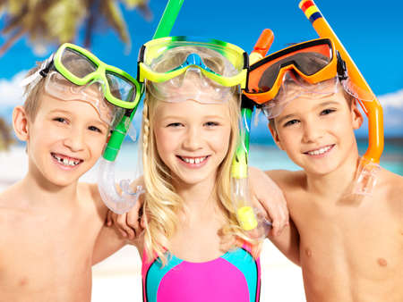 Portrait of the happy children enjoying at beach.  Schoolchild kids standing together in bright color swimwear with swimming mask on head .  photo