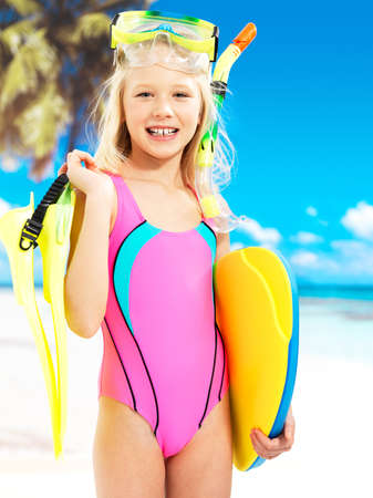 Portrait of the happy girl enjoying at beach.  Schoolchild girl stands  in bright color swimwear with swimming mask on head .  Stock Photo