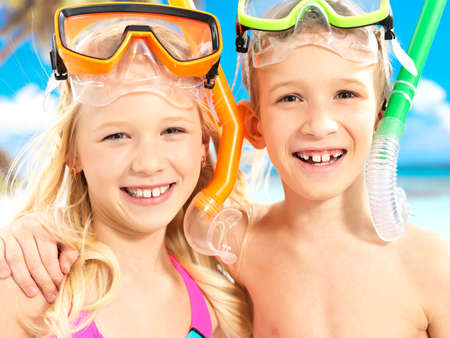 Closeup portrait of the happy brother with sister enjoying at beach.  Laughing children standing together in swimwear with swimming mask on head .  photo