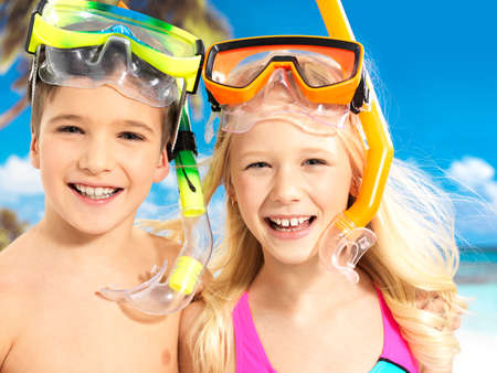 sibling: Portrait of the happy children enjoying at beach.  Brother and sister standing together in swimwear with swimming mask on head .  Stock Photo