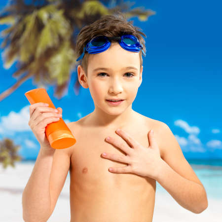 tanned body: Schoolchild boy applying sun block cream on the tanned body.  Boy holding orange sun tan lotion bottle.