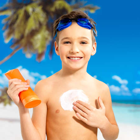 Happy schoolchild boy applying sun block cream on the tanned body.  Boy holding orange sun tan lotion bottle. photo