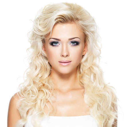 Beautiful woman with long blond curly hair. Portrait of fashion model with bright makeup. Isolated on white photo