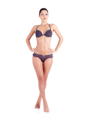 young bikini: Beautiful young woman in a grey bikini with long legs standing isolated on white. Full length portrait