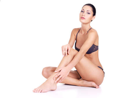 Young woman with health body and long slim legs sits  on white background photo