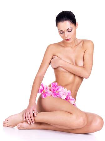 corps femme nue: Jeune femme avec le corps nu est assis sur un fond blanc avec des fleurs Banque d'images