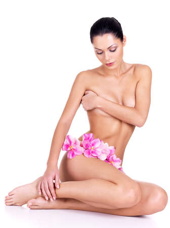 Young woman with nude body sits on the white background with flowers Stock Photo
