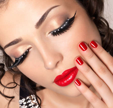 maquillage yeux: Beau mannequin avec des clous rouges, les l�vres et maquillage pour les yeux cr�ative - isol� sur fond blanc