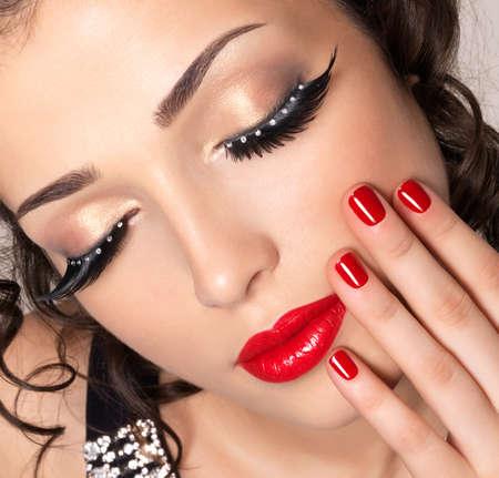 false eyelash: Beautiful fashion model with red nails, lips and creative eye makeup  - isolated on white background Stock Photo