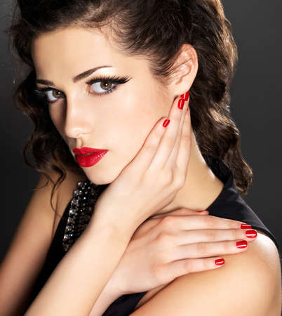 Beauty fashion woman with red nails, lips and golden eye makeup  - on black background Stock Photo - 17642649
