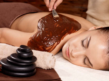 Spa therapy for young woman receiving cosmetic mask on back at beauty salon photo