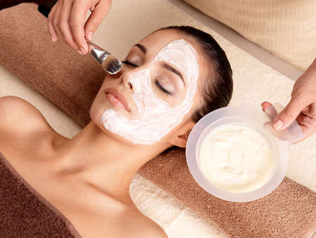 resting mask: Spa therapy for young woman receiving facial mask at beauty salon - indoors