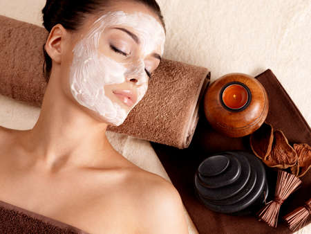 beauty salon face: Young woman relaxing with facial mask on face at beauty salon- indoors Stock Photo