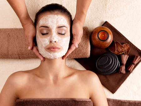 resting mask: Spa massage for young woman with facial mask on face - indoors