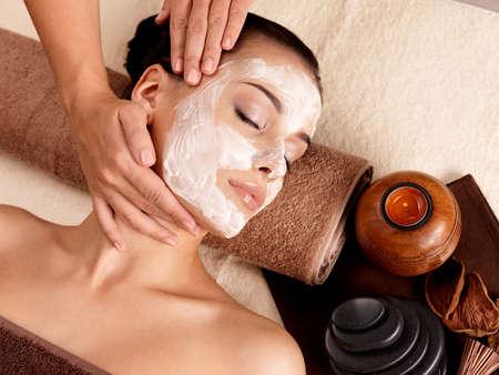 tratamiento facial: Spa masaje para la mujer joven con la máscara facial en el rostro - en el interior