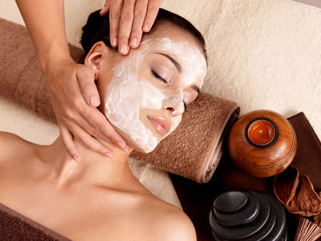 beauty spa: Spa massage for young woman with facial mask on face - indoors