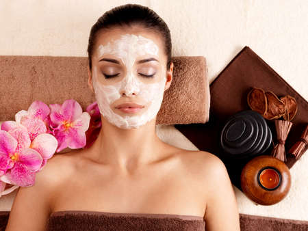 mask face: Young woman relaxing with cosmetic mask on face at beauty salon- indoors