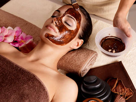 skincare facial: Spa therapy for young woman receving cosmetic mask at beauty salon - indoors