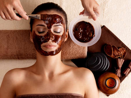 facial spa: Spa therapy for young woman receving cosmetic mask at beauty salon - indoors