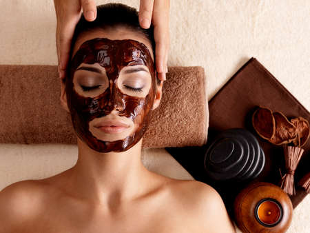 Spa massage for young woman with facial mask on face - indoors photo