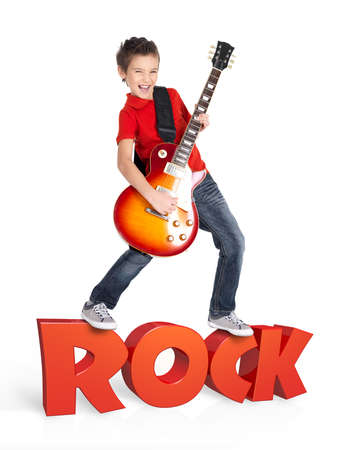 Boy plays  on electric guitar. The boy stands on the word of the rock from the 3d text - isolated on white background Stock Photo