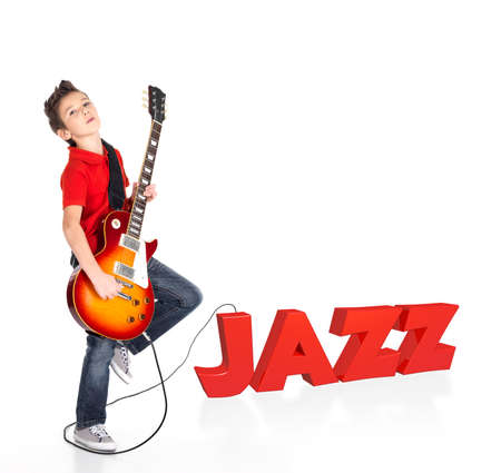 Boy plays  on electric guitar. The boy stands on the word of the juzz from the 3d text - isolated on white background photo