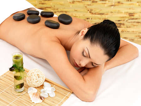 Stone massage for young woman at beauty spa salon. Recreation\ therapy.