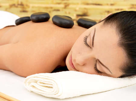masaje: Stone masaje para la mujer joven en el sal�n de belleza spa. Recreaci�n de la terapia. Foto de archivo