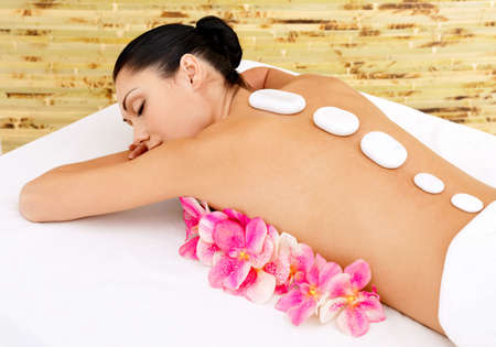 ot: Body care for young woman at beauty spa salon. White нot stones on female back. Stock Photo