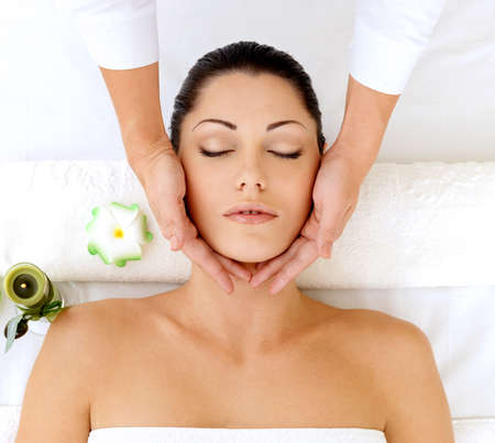 Woman having massage of head in the spa salon. Beauty treatment concept. photo