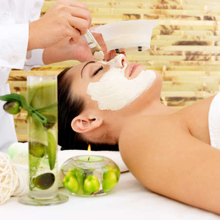 Young woman at spa salon with cosmetic mask on face. High angle photo photo