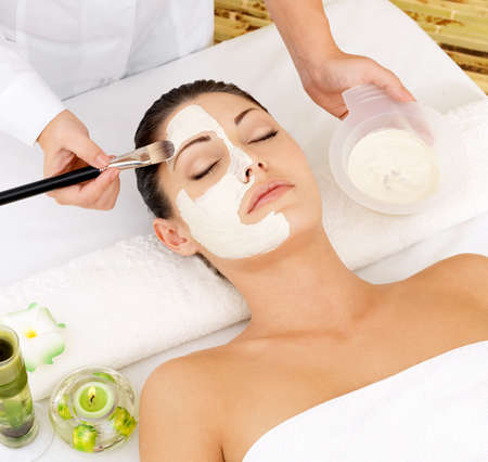 skincare facial: Young woman at spa salon with cosmetic mask on face. High angle photo