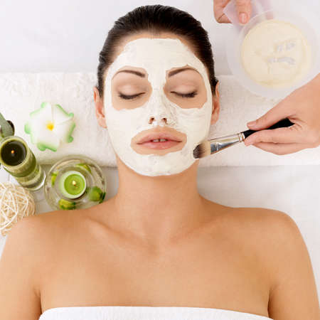 Young woman at spa salon with cosmetic mask on face photo