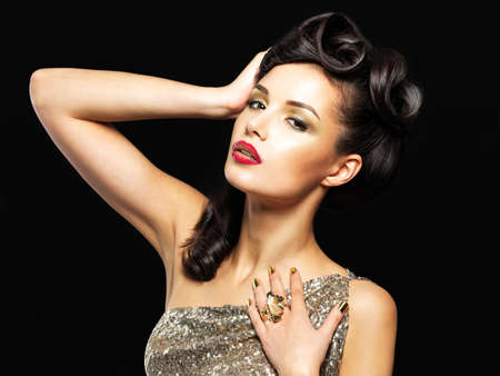 Beautiful  woman with golden nails and fashion makeup of eyes. Brunet girl model with style hairstyle on black background Stock Photo - 17853714