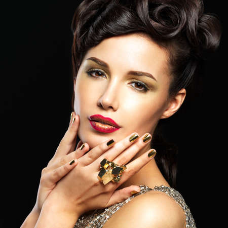 Beautiful  woman with golden nails and fashion makeup of eyes. Brunet girl model with style manicure on black background photo