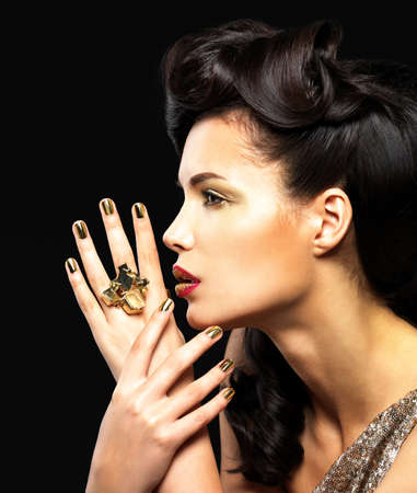 woman face profile: Beautiful  woman with golden nails and fashion makeup of eyes. Brunet girl model with style hairstyle on black background