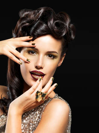 brunets: Beautiful  woman with golden nails and fashion makeup of eyes. Brunet girl model with style hairstyle on black background