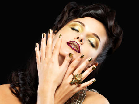 nails: Beautiful brunet woman with golden nails and style makeup of eyes -  on black background