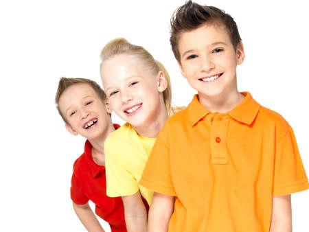 niños felices: Retrato de los niños felices aislados en blanco. Alumno amigos de pie juntos y mirando a la cámara Foto de archivo