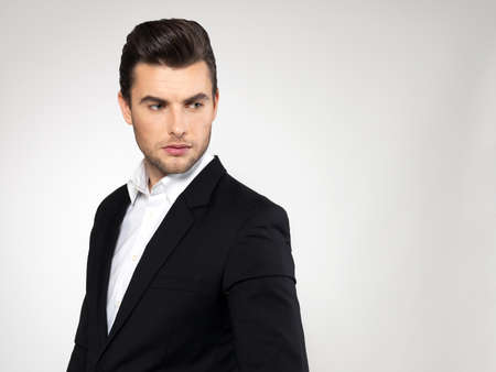 black suit: Closeup face of a fashion young businessman in black suit casual  poses at studio