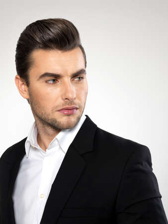man hair: Fashion young businessman black suit casual  poses at studio