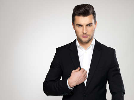 men hair style: Fashion young businessman black suit casual  poses at studio