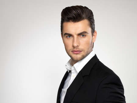 enticement: Fashion young businessman black suit casual  poses at studio